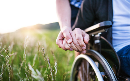 Foto de A close-up of unrecognizable son holding his fathers hand on a wheelchair. - Imagen libre de derechos