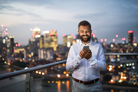 Foto de A businessman with smartphone standing against night London view panorama. - Imagen libre de derechos