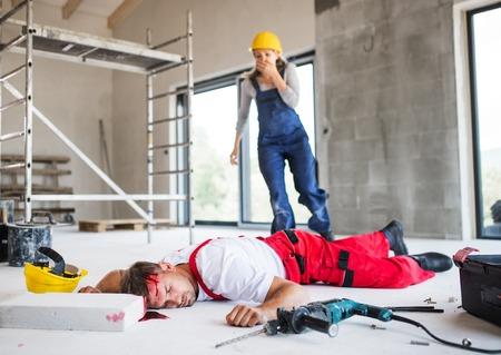 Foto de A woman found man worker lying unconscious on the floor at the construction site. - Imagen libre de derechos