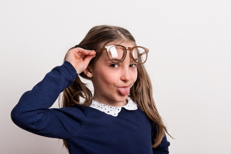 Photo pour A small cheeky schoolgirl with glasses and uniform in a studio, sticking out a tongue. - image libre de droit