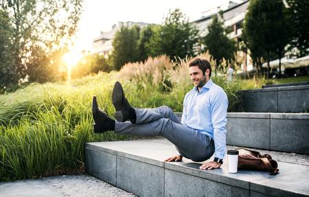 Foto de A happy businessman outdoors on stairs at sunset., handstand in L-sit position. - Imagen libre de derechos