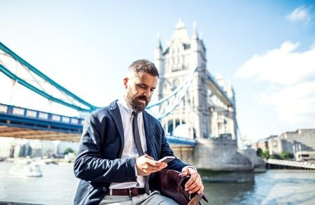 Foto de Hipster businessman with smartphone sitting by the Tower Bridge in London. - Imagen libre de derechos