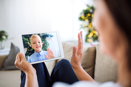 Foto de A grandmother with tablet making videocall with small grandson at Christmas time. - Imagen libre de derechos