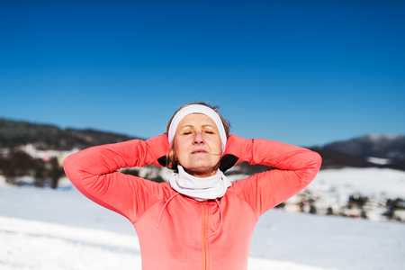 Photo for Senior woman runner resting in winter nature, eyes closed and hands behind head. - Royalty Free Image