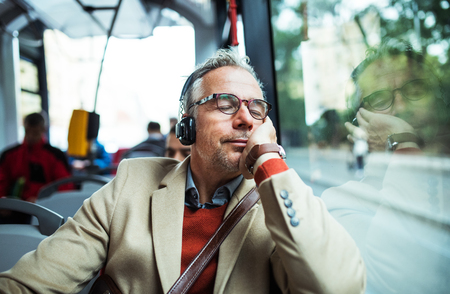 Photo pour Mature tired businessman with heaphones travelling by bus in city. - image libre de droit