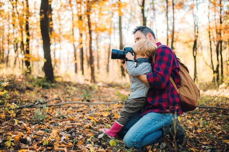 Photo pour A mature father and a toddler son in an autumn forest, taking pictures with a camera. - image libre de droit