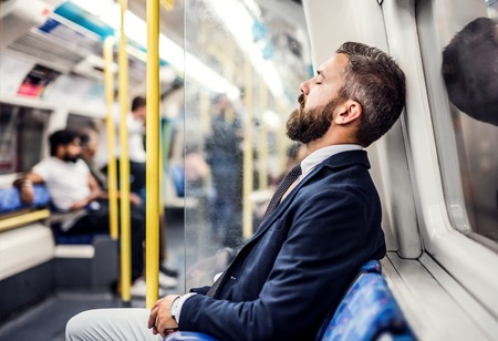 Foto de Sleeping hipster businessman inside the subway in the city, travelling to work. - Imagen libre de derechos
