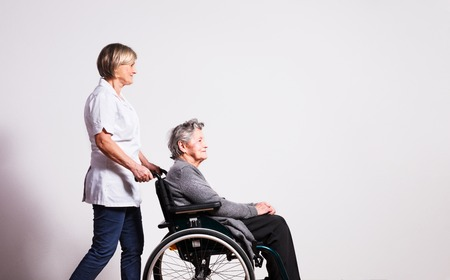 Foto de Studio portrait of a senior woman in wheelchair and a nurse. - Imagen libre de derechos
