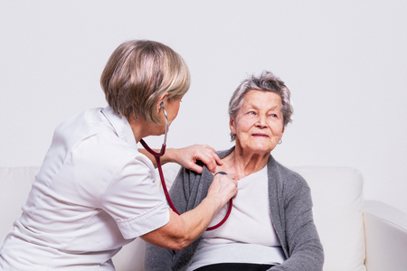 Foto de Studio portrait of a senior nurse examining an elderly woman with a stethoscope. - Imagen libre de derechos