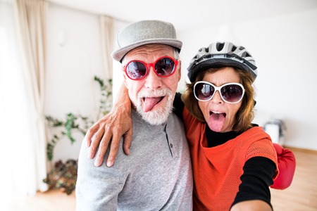 Photo pour A senior couple with sunglasses having fun at home. - image libre de droit