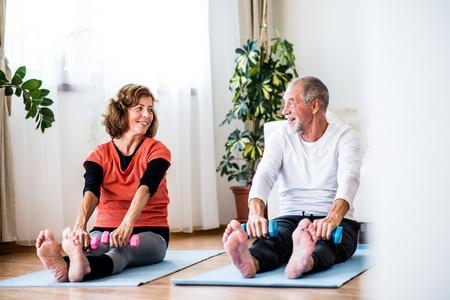 Photo pour A senior couple with dumbbells doing exercise at home. - image libre de droit