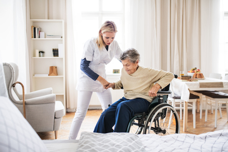 Photo for A health visitor helping a senior woman to stand up from a wheelchair. - Royalty Free Image