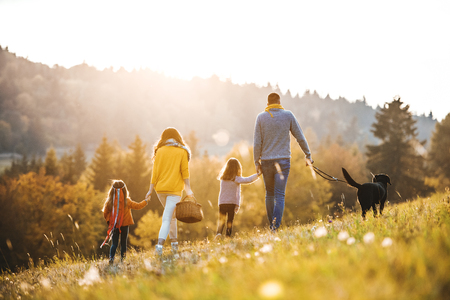 Photo pour A rear view of family with two small children and a dog on a walk in autumn nature. - image libre de droit