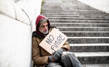 Foto de Homeless beggar man sitting outdoors in city holding no future cardboard sign. - Imagen libre de derechos