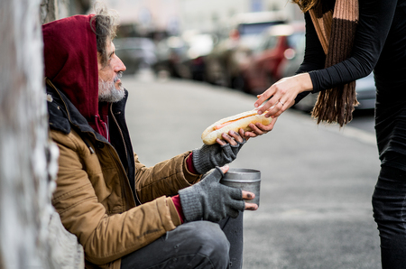 Photo pour Unrecognizable woman giving food to homeless beggar man sitting in city. - image libre de droit