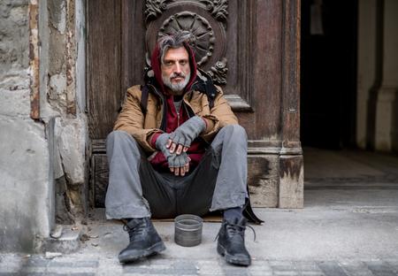 Foto de Homeless beggar man sitting outdoors in city asking for money donation. - Imagen libre de derechos