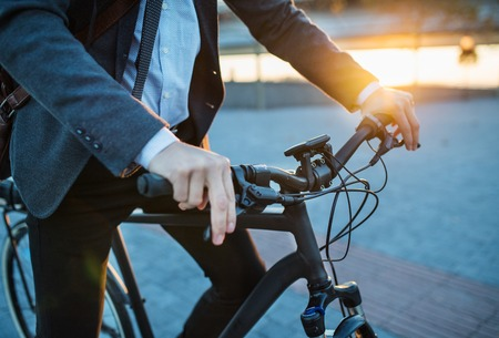 Photo pour Midsection of businessman commuter with electric bicycle traveling from work in city. - image libre de droit