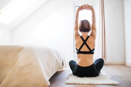 Foto de A rear view of young woman doing exercise indoors in a bedroom. Copy space. - Imagen libre de derechos