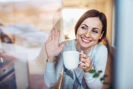 Photo for A young woman with cup of coffee looking out of a window, waving goodbye. - Royalty Free Image