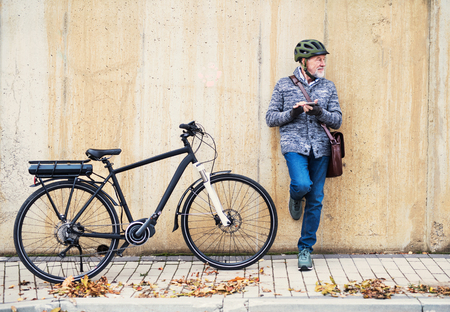 Photo pour Active senior man with electrobike standing outdoors in town, using smartphone. - image libre de droit