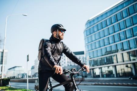 Foto de Male courier with bicycle delivering packages in city. Copy space. - Imagen libre de derechos