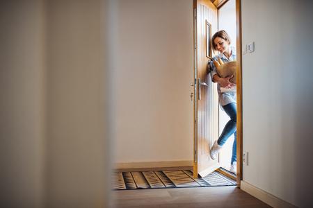 Foto de A young woman with groceries in paper shopping bag walking in through front door. - Imagen libre de derechos