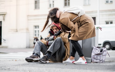 Photo pour Young woman giving money to homeless beggar man sitting in city. - image libre de droit