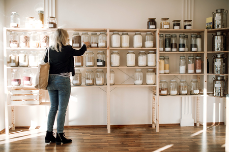 Photo pour A young happy woman buying groceries in zero waste shop. Copy space. - image libre de droit