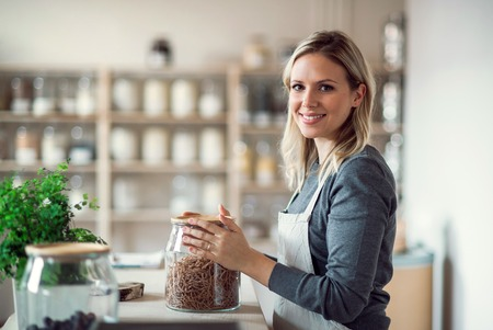 Photo for A female shop assistant in a zero waste shop, holding a jar with groceries. - Royalty Free Image