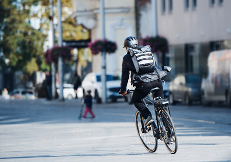 Photo pour A rear view of male bicycle courier delivering packages in city. Copy space. - image libre de droit