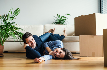 Foto de A young couple with cardboard boxes moving in a new home. - Imagen libre de derechos