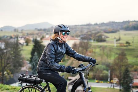 Foto de A side view of senior woman with electrobike cycling outdoors in countryside. - Imagen libre de derechos