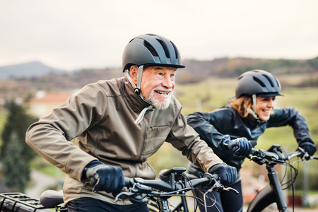 Photo pour Active senior couple with electrobikes cycling outdoors on a road in nature. - image libre de droit