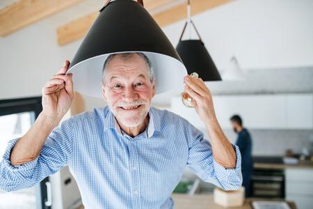 Foto de A senior man helping his son with furnishing new house, a new home concept. - Imagen libre de derechos