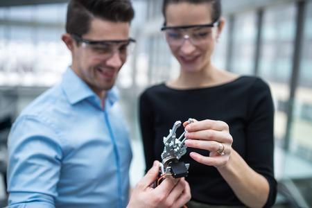 Foto de Two young businesspeople or scientists with robotic hand standing in office, talking. - Imagen libre de derechos