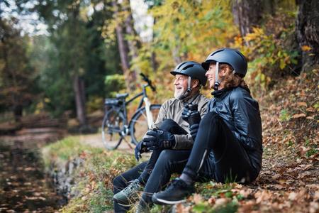 Photo pour A senior couple with electrobikes sitting outdoors in park in autumn, resting. - image libre de droit