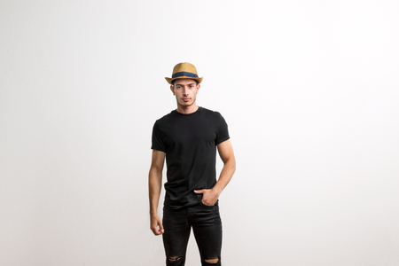 Photo for A confident hispanic young man with hat and black T-shirt in a studio. - Royalty Free Image
