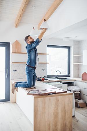 Foto de A mature man furnishing new house, a new home concept. - Imagen libre de derechos