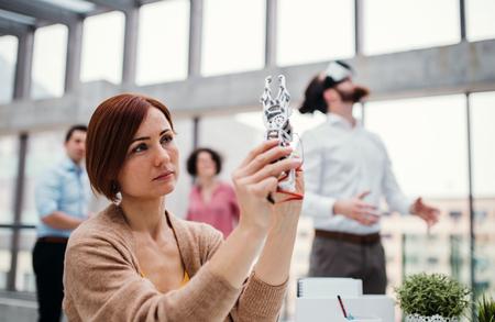 Foto de Young businesswoman or scientist with robotic hand standing in office, working. - Imagen libre de derechos