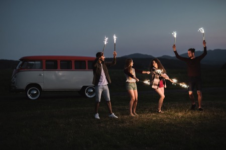 Photo pour A group of friends with sparklers standing outdoors at dusk. - image libre de droit