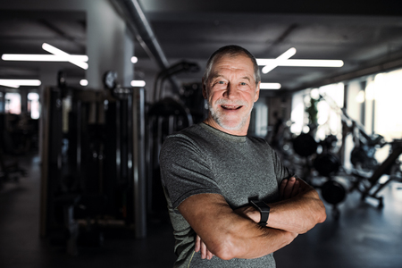 Foto per A cheerful senior man standing in gym, arms crossed. - Immagine Royalty Free