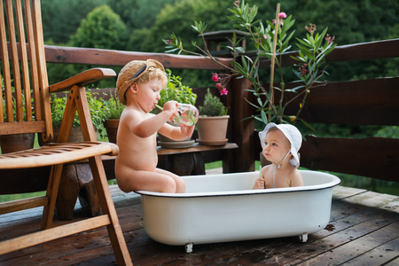 Photo pour Small children with a drink sitting in bath outdoors in garden in summer. - image libre de droit