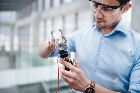 Foto de A young businessman or scientist with robotic hand standing in office, working. - Imagen libre de derechos