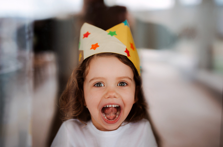 Photo pour A small girl with a paper crown at home, looking at camera. - image libre de droit