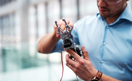 Foto de A midsection of businessman or scientist with robotic hand standing in office, working. - Imagen libre de derechos