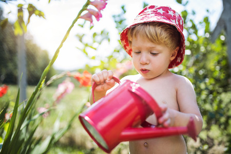 Photo pour Small boy with can outdoors in garden in summer, watering flowers. - image libre de droit