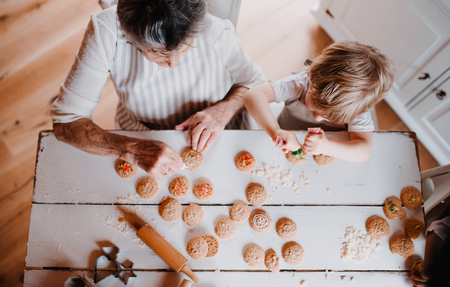 Photo pour A top view of senior grandmother with small toddler boy making cakes at home. - image libre de droit