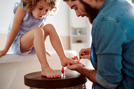 Photo pour Young father painting small daughters nails in a bathroom at home. - image libre de droit