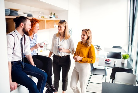 Photo for A group of young business people on coffee break in office kitchen. - Royalty Free Image