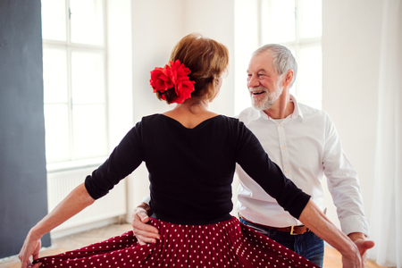 Photo for Senior couple attending dancing class in community center. - Royalty Free Image